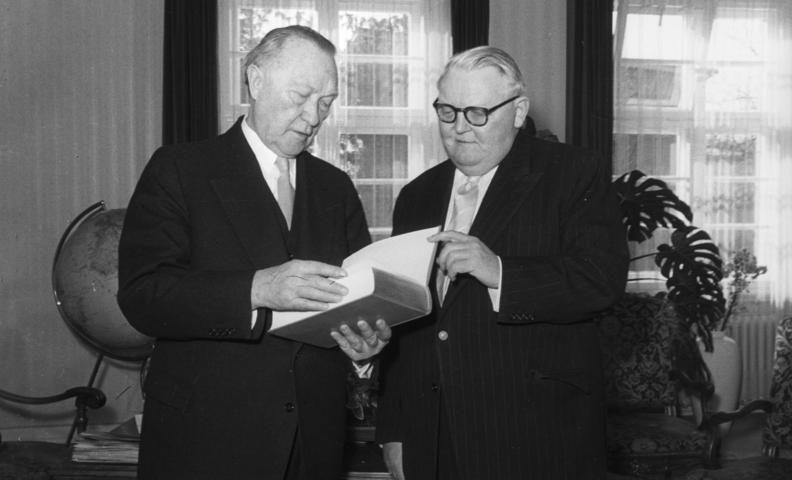 Bundeskanzler Konrad Adenauer liest interessiert in dem Buch, das ihm Bundes-Wirtschaftsminister Prof. Erhard als Geburtstagsgeschenk überreichte.