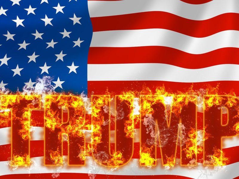 USA-Flagge mit Trump-Schriftzug in Flammen