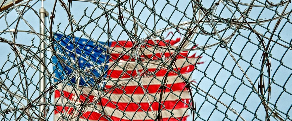 US-Flagge hinter Stacheldraht